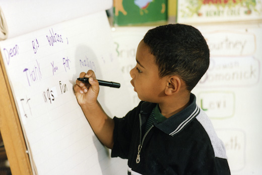 Young child writing on chart paper